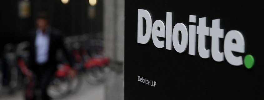 Deloitte sign with person walking in background