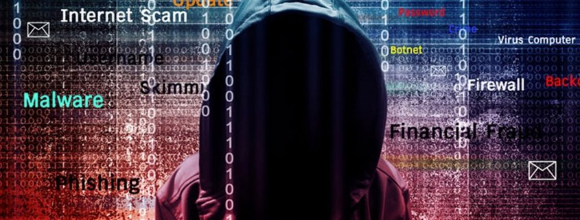 Person in dark hoodie with cybersecurity keywords floating