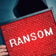Person in hooded sweatshirt holding picture with the word ransom on it