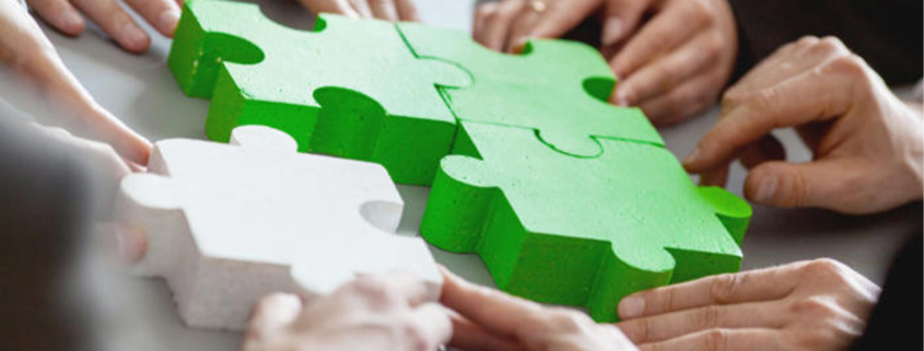 Business people putting together a puzzle as partners